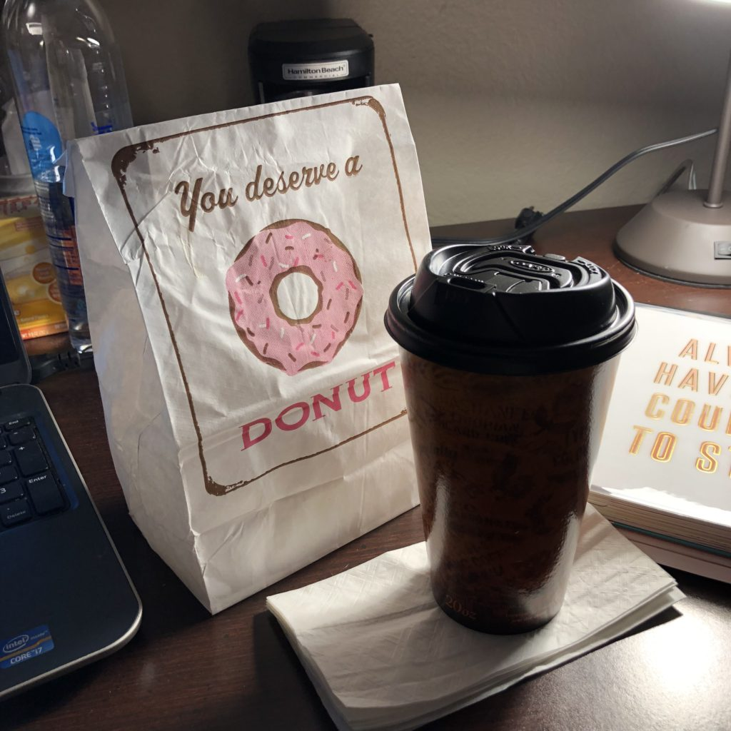 Bag of donuts and cup of coffee beside an Erin Condren Life Planner.