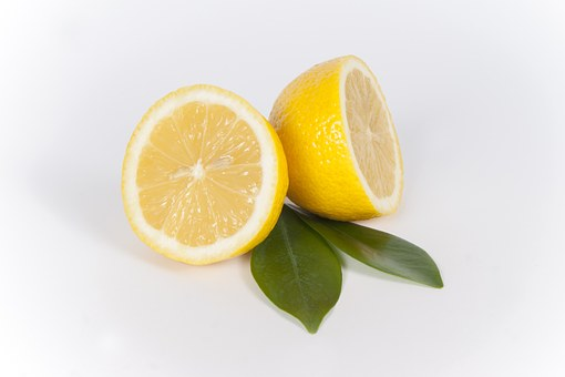 A fresh lemon arranged in two halves against a pair of green leaves.