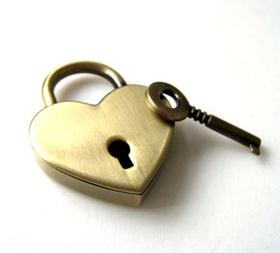 a brass heart-shaped lock lays beside a brass key