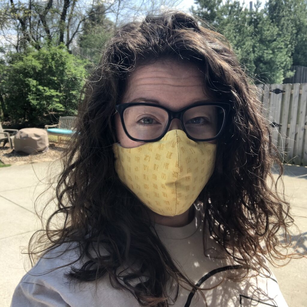 The author is shown wearing a yellow face mask.
