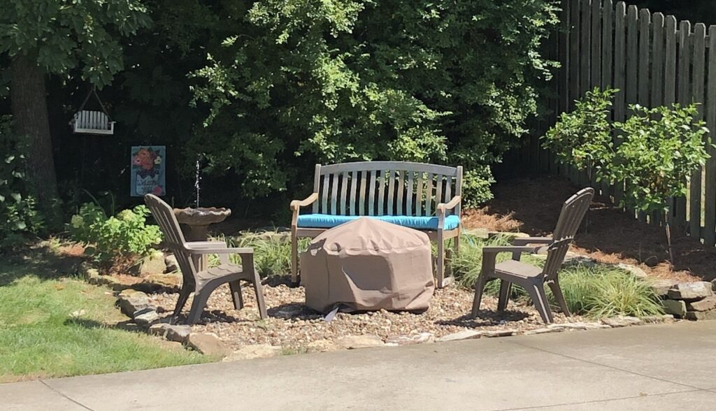 A gravel fire pit area is shown with a pair of plastic Adirondack chairs and a wooden bench seat.